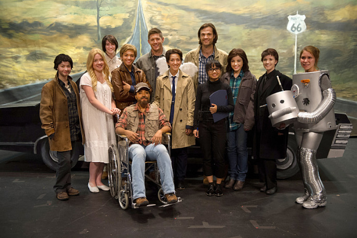"""Supernatural -- """"Fan Fiction"""" -- Image SN1005d_0274 -- Pictured (back row center L-R): Jensen Ackles as Dean and Jared Padalecki as Sam surrounded by cast of Supernatural: The Musical!"""" -- Credit: Diyah Pera/The CW -- © 2014 The CW Network, LLC. All Rights Reserved"""