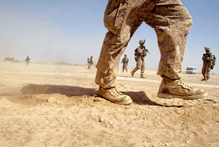 U.S. Marines from the 2nd Marine Expeditionary Battalion walk through the sand inside Camp Leatherneck in Afghanistan's Helmand province Monday June 8, 2009. Some 7,000 of the new U.S. troops ordered to Afghanistan are fanning out across the dangerous south on a mission to defeat the Taliban insurgency and to change the course of a war claiming American lives at a record pace. (AP Photo/David Guttenfelder)