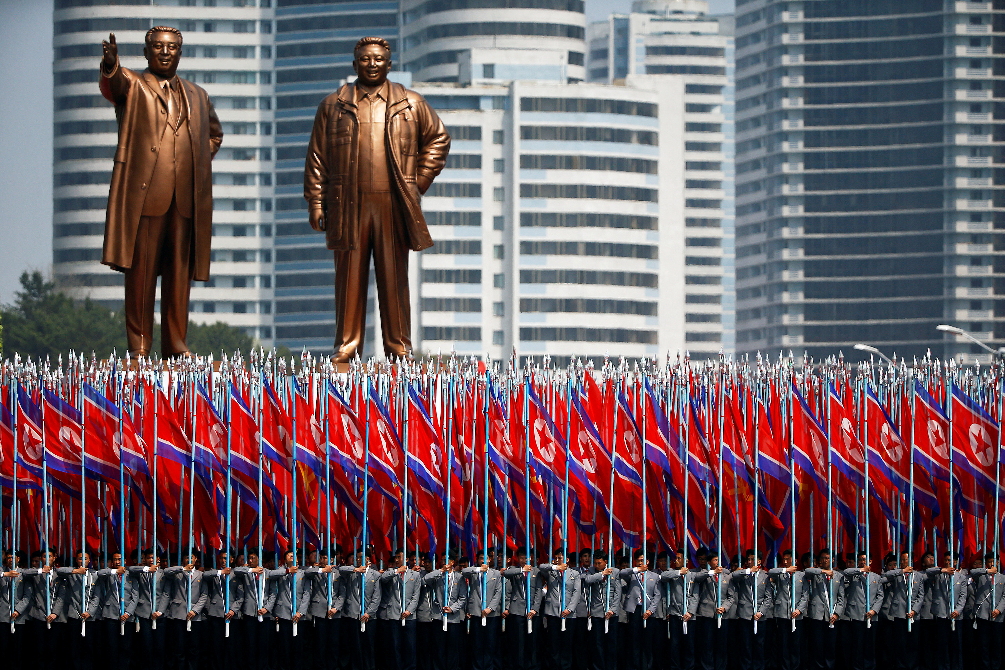 "People carry flags in front of statues of North Korea founder Kim Il Sung (L) and late leader Kim Jong Il during a military parade marking the 105th birth anniversary Kim Il Sung, in Pyongyang April 15, 2017. The men carrying flags are wearing North Korean university uniforms. The float containing the statues is often marks the start of a section of the parade led by people chosen to represent ordinary citizens, as opposed to soldiers or military equipment. Once the parade is over, and the float has completed its official function, a large white sheet is placed over each statue in order to preserve the ""Supreme Dignity"" of each figure as the float meanders its way back through the city amid normal traffic. REUTERS/Damir Sagolj SEARCH ""PARADE WID"" FOR THIS STORY. SEARCH ""WIDER IMAGE"" FOR ALL STORIES. - RTS12G64"